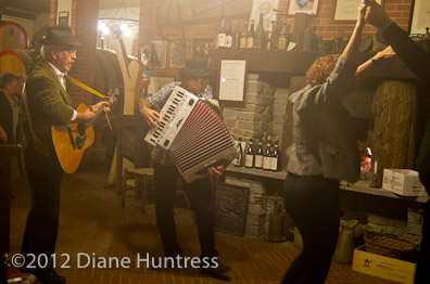 Piemontese accordian and guitar playing, people dancing in wine cellar