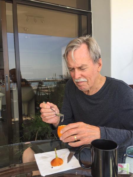 man eating exotic orange fruit with stem